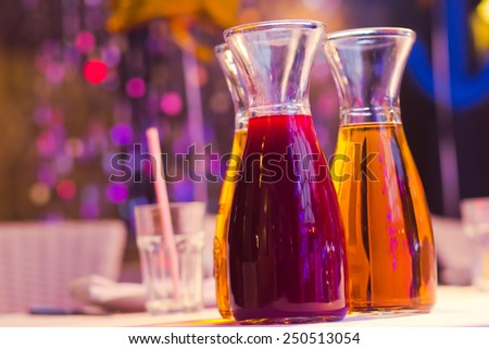 Beautiful line of different colored cocktails with smoke on a Christmas party, tequila, martini, vodka, and others on decorated catering bouquet table on open air party, jug pitcher with juice - stock photo