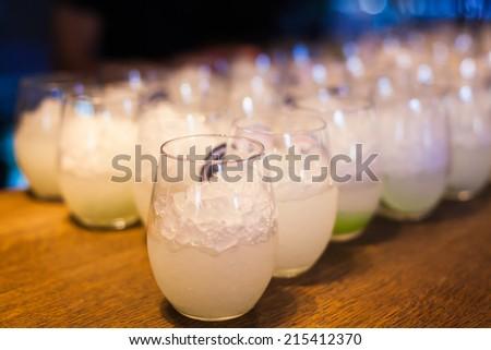Beautiful line of different coloured cocktails on a open air party, tequila, martini, vodka, and others on decorated catering table on open air party  - stock photo