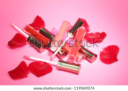beautiful lip glosses with rose petals, on pink background