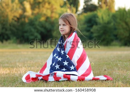 Beautiful little American in jeans sits on a large American flag and looking into the distance