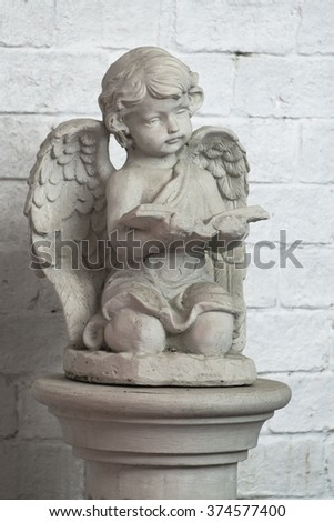 Beautiful little angel statue. Detail and portrait of sitting and reading cupid.
