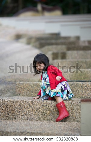 Beautiful little asian girl wear red boots and try to walking down on stone stair in the Phuket Bird Park show.