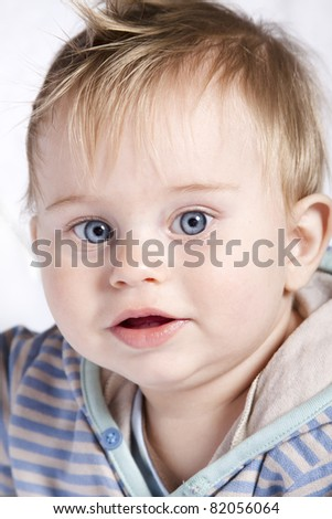 Beautiful little baby boy playing on white blanket 9 months old - stock photo