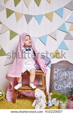 Beautiful little baby boy sitting on a chair with a knitted blanket Easter basket