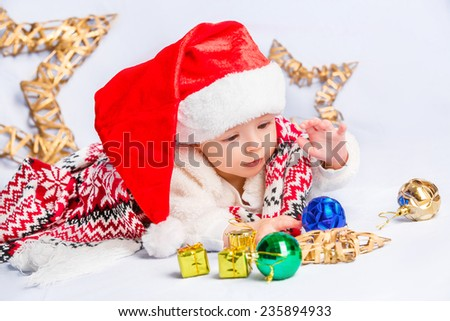 Beautiful little baby celebrates Christmas. New Year's holidays. Baby in a Christmas costume and in santa hat