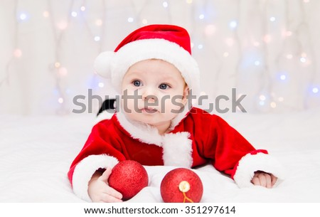Beautiful little baby celebrates Christmas. New Year's holidays. Baby in a Christmas costume with ball