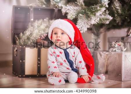 Beautiful little baby celebrates Christmas. New Year's holidays. Child in a Xmas costume with gift. Santa Kid with a red hat sitting near Christmas tree - stock photo
