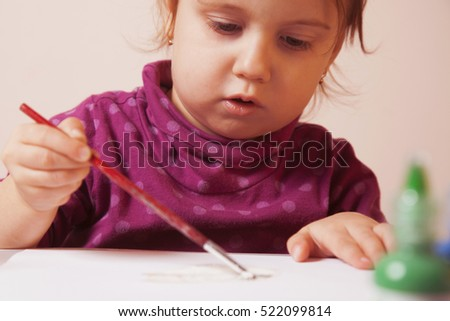 beautiful little baby girl draws a picture paints (postmodernism, talent, creativity, creativity)