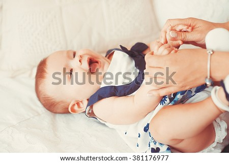 Beautiful little baby girl lies on a light carpet with mom. happy mother with baby