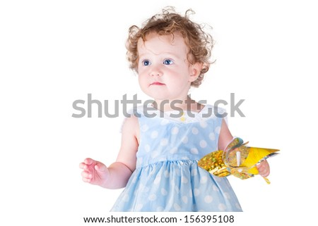 Beautiful little baby girl playing with a wind toy wearing a nice blue dress, isolated on white