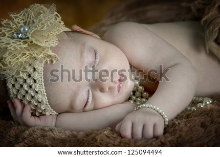 Beautiful little baby girl with bow and pearls sleeping peacefully on fur blanket - stock photo
