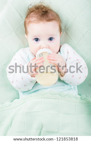 Beautiful little baby with a milk bottle under a warm knitted blanket - stock photo