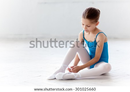 Beautiful little ballerina in blue dress for dancing sitting on the floor and puting on foot pointe shoes on white ballet studio background - stock photo