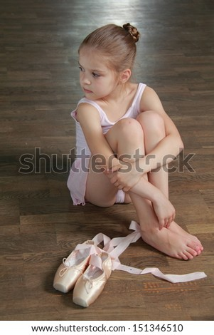 Beautiful little ballerina wearing tutu and posing on camera - stock photo