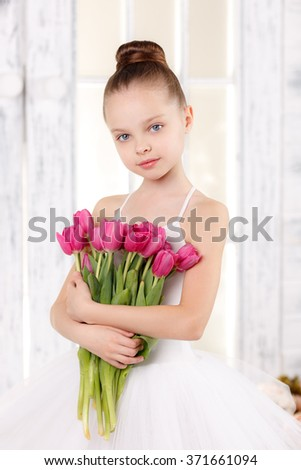 beautiful little ballerina with a bouquet of pink tulips, March 8 - stock photo