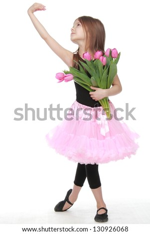 Beautiful little ballerina with long healthy hair in a pink tutu dancing ballet with tulips on Beauty - stock photo