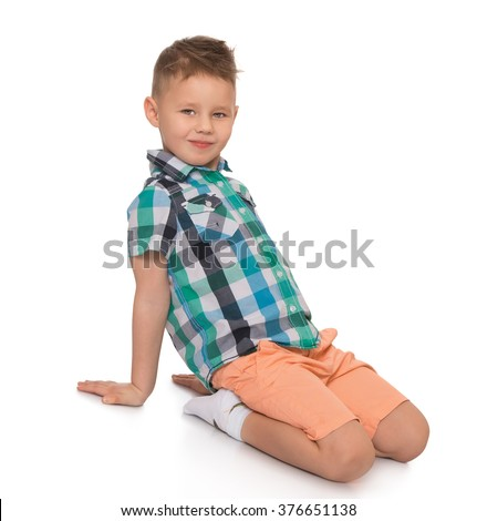 Beautiful little blond boy with a fashionable haircut, wearing a checkered shirt and pink shorts is sitting on the floor - Isolated on white background