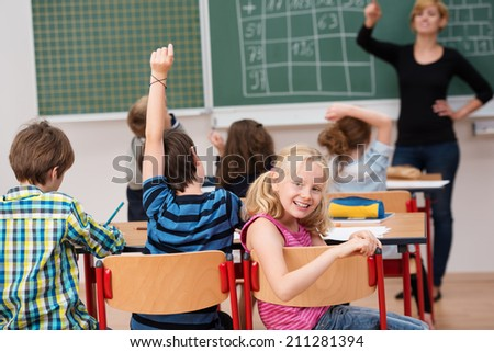 Beautiful little blond girl sitting in class turning to smile at the camera as the teacher takes questions from the rest of her classmates - stock photo