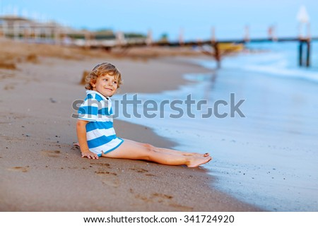 Beautiful little blond kid boy having fun with building sand castle on the beach of ocean or see by sunset. Happy child spending active vacations. - stock photo