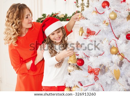 Beautiful  little blonde girl and her mother, has fun smiling face, red hat Santa Claus, sits near christmas tree, holding tree toy.