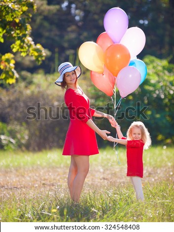 Beautiful little blonde girl and her mother, has happy fun cheerful smiling face, red dress, multicolored balloons. Family portrait nature.  - stock photo