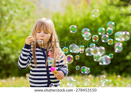 Beautiful little blonde girl, playing outdoor, springtime, late sunny afternoon - stock photo