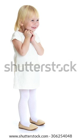 Beautiful little blonde girl with a short haircut Bob in a white short dress . Girl looking to the side with folded hands - stock photo