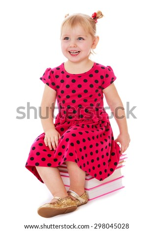 Beautiful little blonde girl with short hair and ponytails on her head in a red long dress with polka dots sitting on a stack of books , the girl prepares to become a schoolgirl-Isolated on white