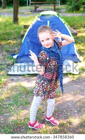 Beautiful little blue eyes girl in a park near a tree on the background of nature in a scarf