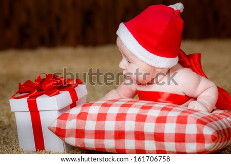 beautiful little boy Christmas hat with a gift - stock photo