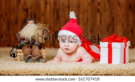beautiful little boy Christmas hat with a gift. looks in the picture - stock photo