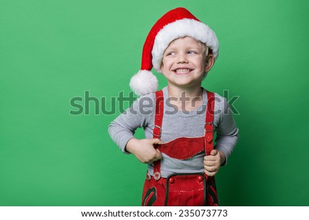 Beautiful little boy dressed like Christmas elf with big smile. Christmas concept. Studio portrait over green background