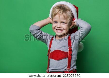 Beautiful little boy dressed like Santa Claus helper smiling. Christmas concept. Studio portrait over green background    - stock photo