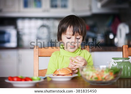 Beautiful little boy, eating sandwich at home, vegetables on the table - stock photo