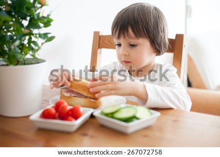 Beautiful little boy, eating sandwich at home, vegetables on the table, back light - stock photo