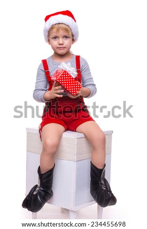 Beautiful little boy holding present from Santa Claus. Christmas. Studio portrait isolated over white background   - stock photo