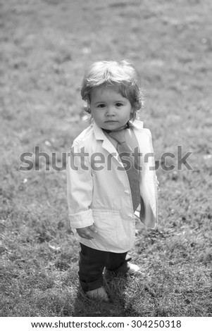 Beautiful little boy kid with curly hair in unbuttoned shirt necktie and trausers standing barefoot on fresh grass yard sunny day outdoor on natural background black and white, vertical photo - stock photo