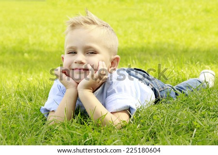 beautiful little boy lies on meadow and smiling - stock photo