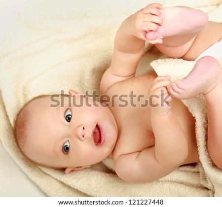 beautiful little boy lying on beige towel - stock photo