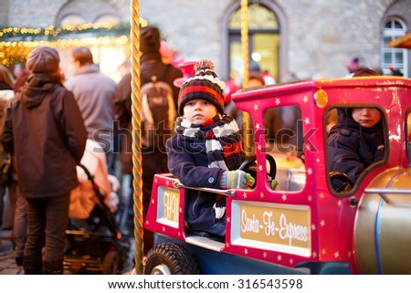 Beautiful  little boy on a carousel at Christmas funfair or market, outdoors. Happy child having fun. Traditional xmas market in Germany, Europe. Holiday, children, lifestyle concept. - stock photo
