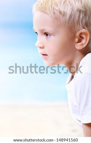 Beautiful little boy on the beach - stock photo