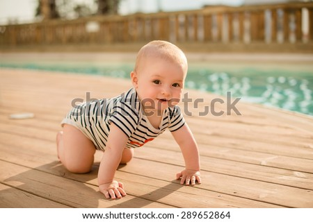beautiful little boy sitting in pool - stock photo