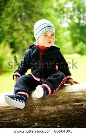 Beautiful little boy sitting outdoors