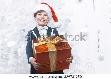 Beautiful little boy with a big Christmas gift in a Santa Claus hat. Christmas gifts for children. Smart boy Celebrates Christmas. New Year's holidays - stock photo