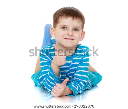 Beautiful little boy with a blue striped t-shirt lying on the floor and shows the hand gesture OK  - stock photo