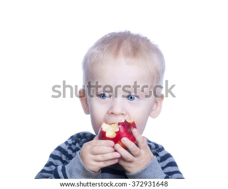 Beautiful little boy with blond hair and blue eyes is holding an apple and eats. The child eats red apple.