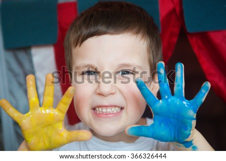 Beautiful little boy with hands in the paint - stock photo