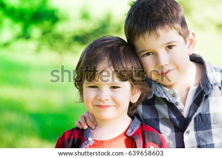 Beautiful little brunet hair boys, has happy fun smiling face, brown eyes, plaid shirt. Child portrait. Creative concept. Close up. Blood brothers. Summer time.