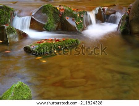 Beautiful little cascade waterfall in autumn forest - stock photo