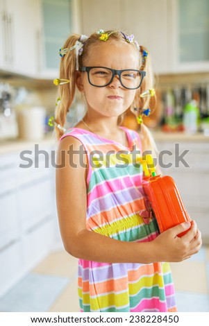 Beautiful little cheerful girl with glasses holding red toy box. - stock photo